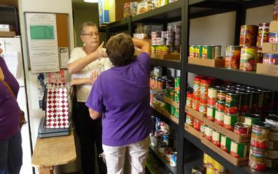 Kelly and Donna work side by side to provide food for clients.